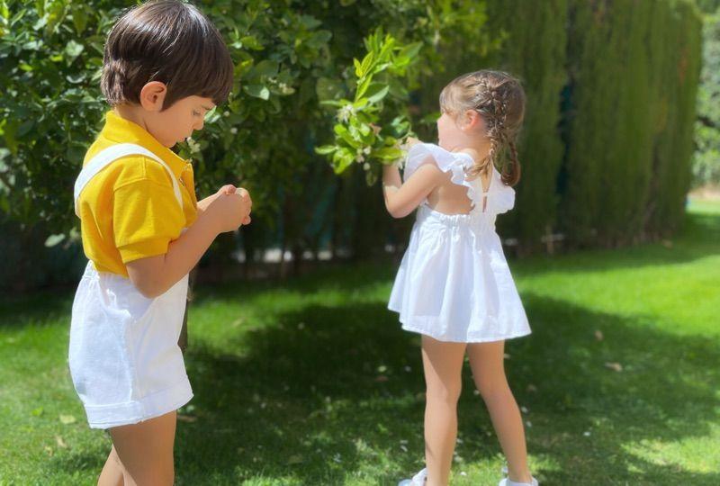 peto vaquero blanco con polo amarillo de niño y vestido blanco de volantes de niña